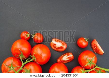 Cherry tomatoes and halves of tomatoes on a black background