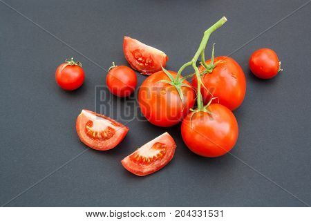 Cherry tomatoes and a piece of cherry on a black background