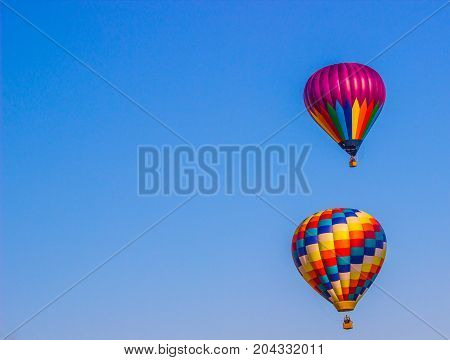 Two Multi Colored Hot Air Balloons In Early Morning