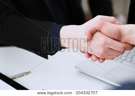 Two businessman shake hands as hello in office closeup. Friend welcome introduction greet or thanks gesture product advertisement partnership approval arm strike a bargain on deal concept