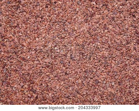 Close-up sand texture, modern coating for running tracks. Image of cover athletic fields in close proximity. A lot of small red glitter stones. Abstract orange color asphalt.