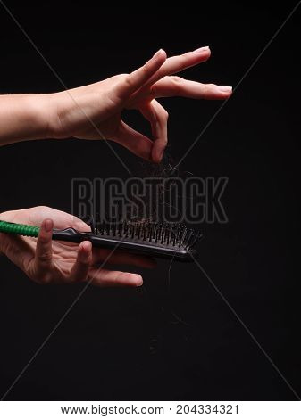 Stress to comb long brown hair. Close-up photo of female hands with hair. Hair loss.