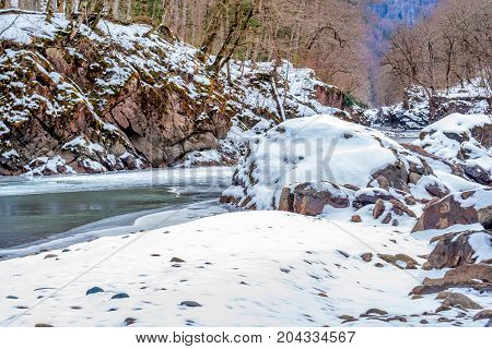 Beautiful winter landscape with turquoise mountain river chained with ice and granite canyon covered with snow
