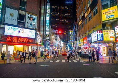 TOKYO, JAPAN JUNE 28 - 2017: Unidentified people walking and enjoying the beautiful famous Kabukicho red lights district, surrounding of big buildings and advertisements in the night, located in Tokyo, Japan.