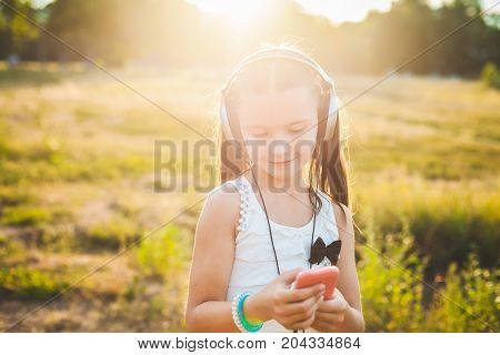 Joyful girl choosing music on mobile telephone and joyfully smiling, cute child resting on nature with music
