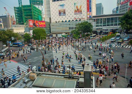 TOKYO, JAPAN JUNE 28 - 2017: Top view of crowd of people crossing in Shibuya street, one of the busiest crosswalks in the world, in the Ginza District in Tokyo, Japan.