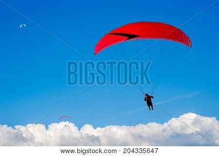 The paraglider hovers in the sky high above the clouds