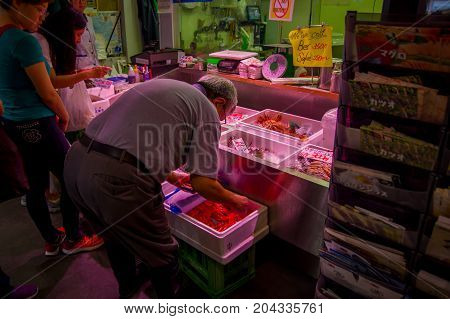 TOKYO, JAPAN JUNE 28 - 2017: Unidentified people selling and buying seafood packed inside of plastic boxes at Fish Market Tsukiji wholesale in Tokyo Japan, Tsukiji Market is the biggest wholesale fish and seafood market in the world.