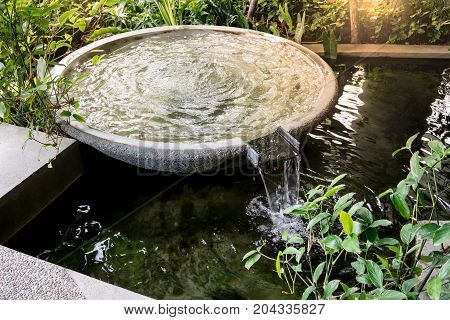 Circle shape water fountain and water fall in garden or park. Landscape design