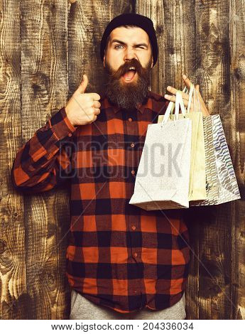 Bearded man long beard. Brutal caucasian satisfied hipster with moustache holding shopping packages in red black checkered shirt on brown wooden vintage studio background