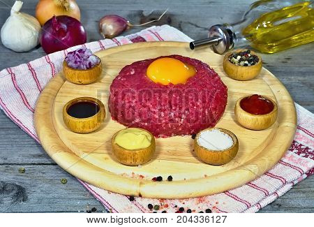 Tartar beef with ingredients for its preparation. Food meat yolk pepper salt and worchester sauce.