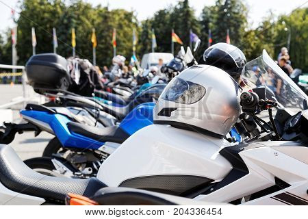 Light silver moto helmet on motorcycle and motorbikes on blurred background