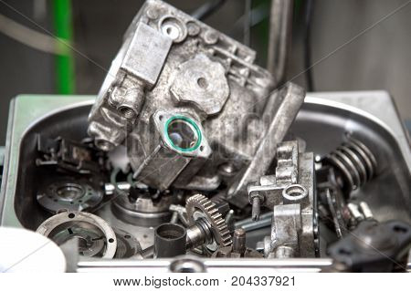 Close up The disassembled mechanical high-pressure diesel pump lies in a metal container. Components of the mechanism. Service of maintenance of diesel equipment