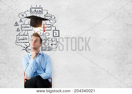 Thoughtful young businessman sitting on concrete wall background with mortarboard copy space and educational sketch. Graduation concept