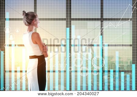 Side view of young woman in office with city view and business chart hologram. Innovation and economy concept. Double exposure