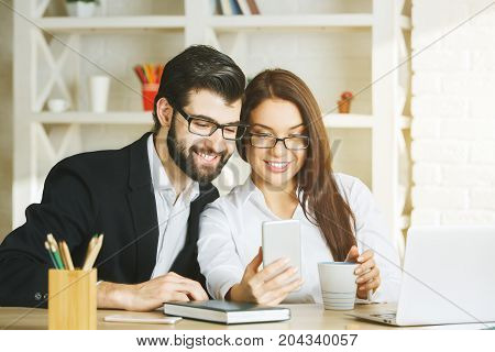 Smiling Businessman And Woman Using Smartphone