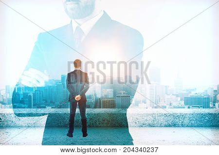 Thoughtful young businessman standing on concrete rooftop and looking into the distance. Think concept. Double exposure