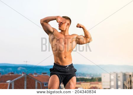 Man Flexing Muscles On A Rooftop