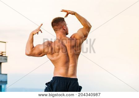 Bodybuilder Flexing Muscles On A Rooftop