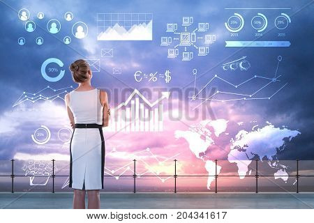 Back view of young businesswoman standing on rooftop with abstract business charts and diagrams on city and sky background. Future and ecnomy concept. Double exposure