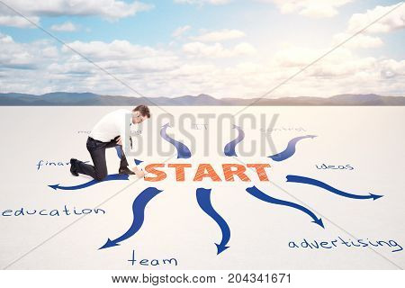 Businessman drawing abstract business sketch in desert. Sky with sunlight in the background. Startup concept
