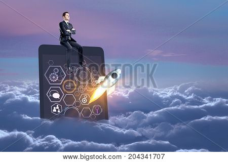 Abstract image of businessman sitting on tablet with business sketch and launching rocket in sky with clouds and sunset. Startup concept