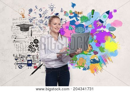 Smiling young businesswoman with laptop standing on concrete wall background with business sketch. Education concept