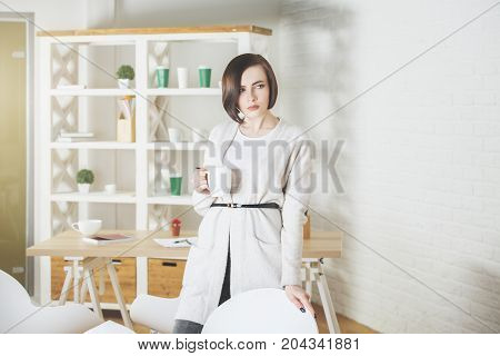 Portrait of pretty european woman drinking coffee or tea while standing in modern office with items on shelves. Morning breakfast break energy boost concept