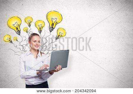 Smiling young businesswoman with laptop standing on concrete wall background with light bulb sketch. Idea concept