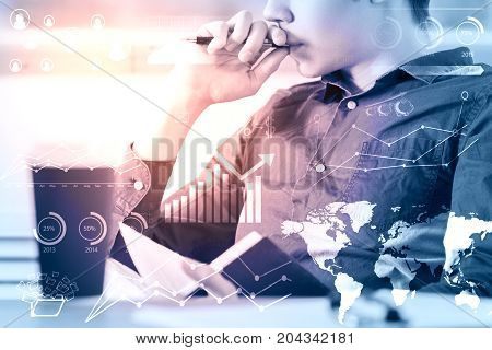 Side view of young businessman sitting at workplace with book coffee cup and business hologram. Finance concept. Toned image. Double exposure