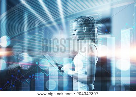 Side view of attractive woman using tablet on creative night city background with business chart. Technology and economy concept. Double exposure