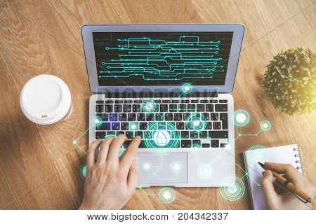 Top view of businessman hands using laptop with digital hologram and writing in notepad on wooden desktop with coffee cup and decorative plant. Innovation concept