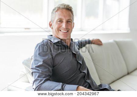 A Portrait of single 40s man sitting in sofa