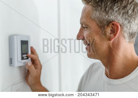 A Smiling Man Adjusting Thermostat On Home Heating System