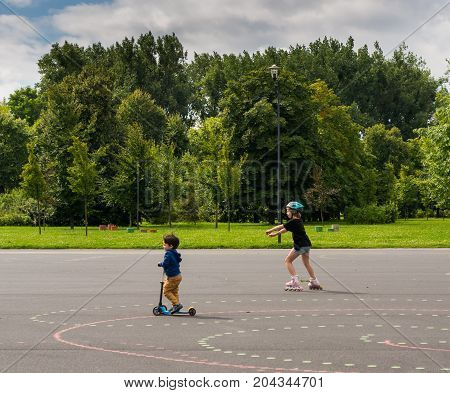Toddler on child scooter and girl on rollerskates on asphalt at a park on a cloudy day on August 2017 in Poznan Poland