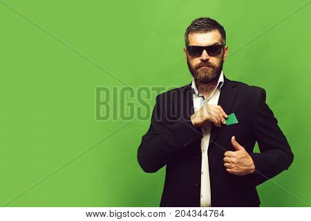 Man With Beard Puts Business Card Into Suit Pocket