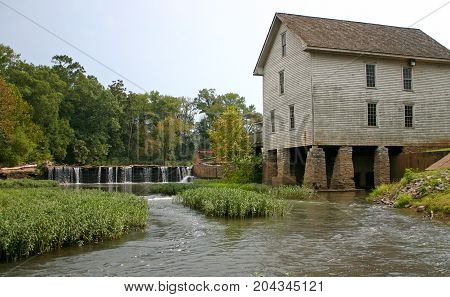 water flows over a small dam next to a gristmill