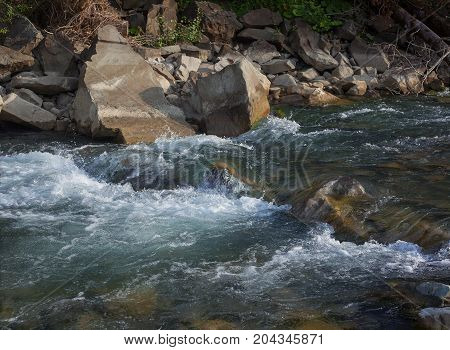Rapid mountain river in a stone channel