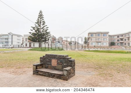 SWAKOPMUND NAMIBIA - JUNE 30 2017: A memorial bench with holiday apartments in the back in Swakopmund in the Namib Desert of Namibia