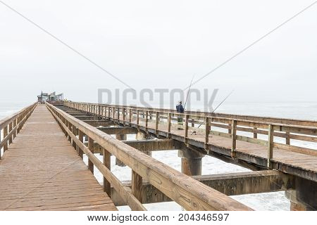 SWAKOPMUND NAMIBIA - JUNE 30 2017: An angler on the historic jetty with a restaurant on its far end in Swakopmund in the Namib Desert on the Atlantic Coast of Namibia