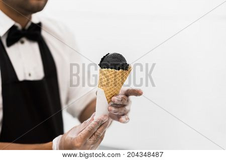 Handsome young waiter in elegant classic suit serving trendy dessert, black ice cream in traditional portioned waffle cone. Uninsulated white background, copy space. Real scene. Professional service, catering concept