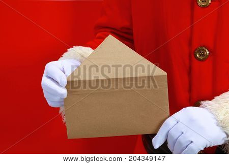 hand of Santa Claus with a letter on a red background.
