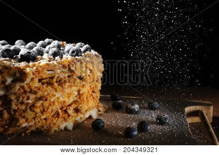 layer cake Napoleon with berries blueberry on a rough wooden tray, sprinkle with powdered sugar black background for menu cafe or patisserie.