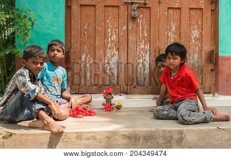 Mysore India - October 27 2013: Four small kids in colorful shirts sit and play in front of house with clay figurines looking into camera. Brown and green background.