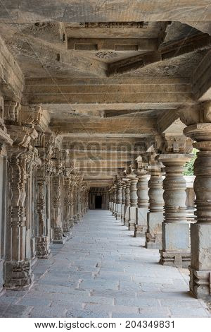 Mysore India - October 27 2013: Portrait shot of beige stone columned corridor along outside wall of Chennakesava Tempel in Somanathpur village. Ceilings and row of pillars till the end.