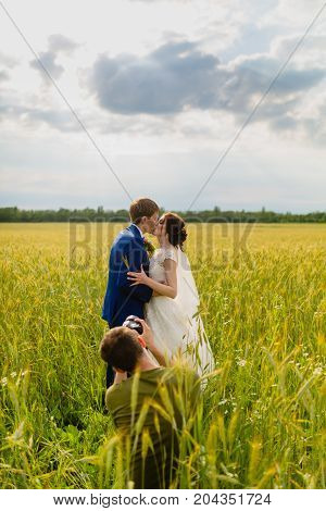 Photographermaking close-up portraits of newlyweds in a field