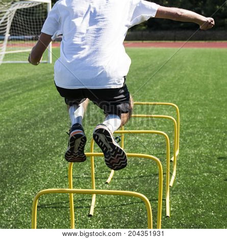A runner bounding over yellow hurdles on a green turf field during track and field practice to help produce power agility and strength.