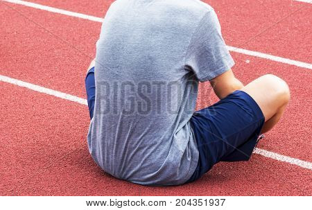 A high school boy stretches on a track before cross country practice.