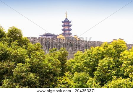 Jiming Temple rising above the historic wall in the city of Nanjing located in Jiangsu province China.