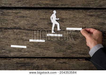 Creative concept of a successful businessman climbing the corporate ladder with paper silhouette cutouts and a male hand building the staircase on rustic wood with copy space.